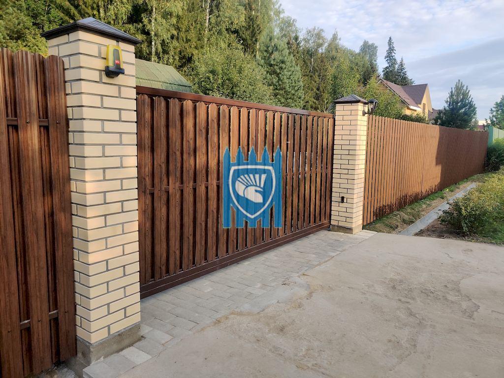 Забор из евроштакетника под дерево с кирпичными столбами и откатными воротами в Рузе 4